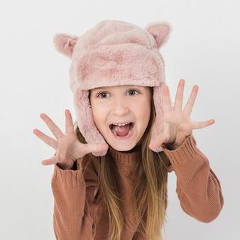 Chica rubia haciendo muecas con sombrero de invierno