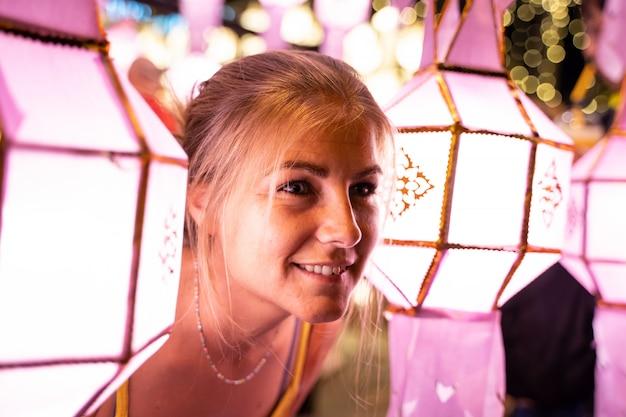Chica rubia iluminada por faroles chinos en la noche