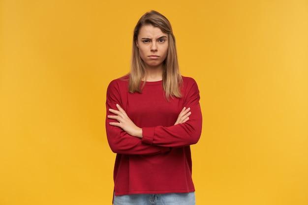Chica rubia insatisfecha se ve indignada, con una ceja levantada, vestida con ropa informal