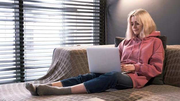 Chica rubia joven creadora de contenido está en su computadora portátil sentada en el sofá cerca de la ventana