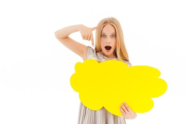 Chica rubia joven sorprendida en vestido sosteniendo una nube de discurso en blanco y apuntando sobre ella en blanco