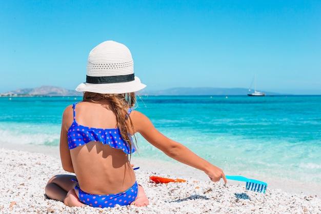 Chica rubia jugando con la arena en la playa