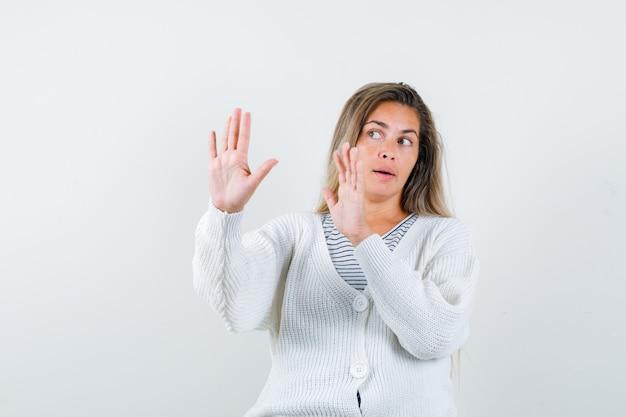 Chica rubia levantando las manos en pose de rendición con camiseta a rayas, cárdigan blanco y pantalones de mezclilla y mirando asustada. vista frontal.