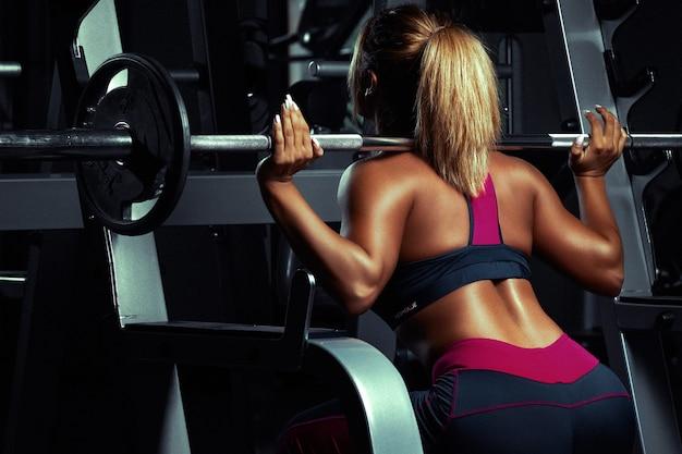 Chica rubia levantando pesas sobre los hombros, vista posterior