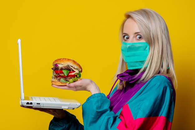 Chica rubia en mascarilla con hamburguesa y computadora portátil