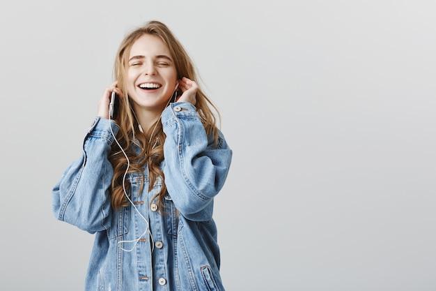 Chica rubia optimista disfrutando de escuchar música, sonriendo encantado