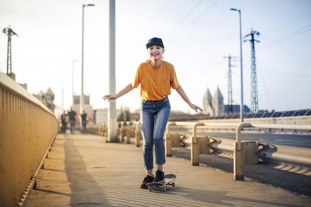 Chica rubia patinando en la ciudad