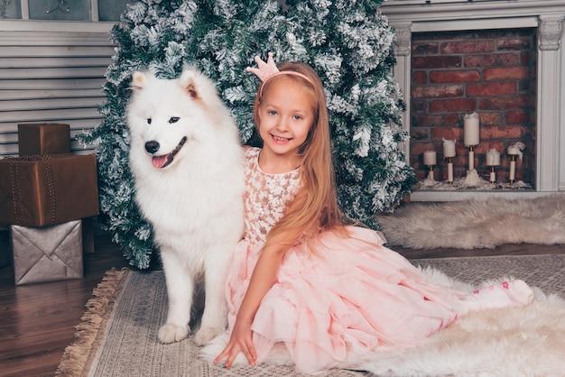 Chica rubia y perro samoyedo por el árbol de año nuevo.