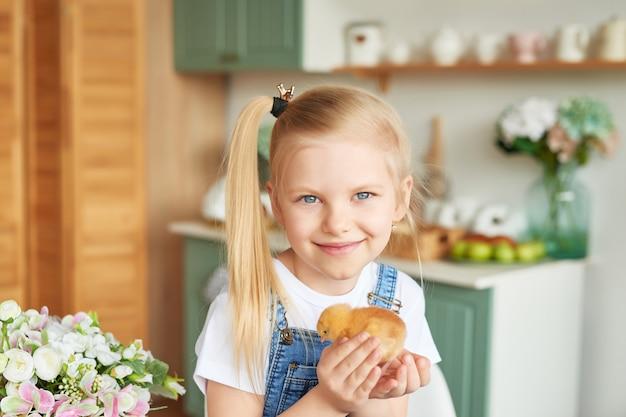 Chica rubia con pollos de pascua en la cocina de estilo provenzal