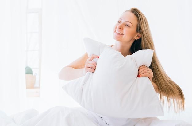 Chica rubia posando en la cama