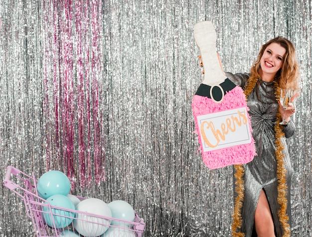 Chica rubia posando en fiesta de año nuevo con botella de cartón