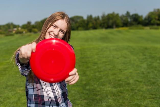 Chica rubia posando con un frisbee rojo