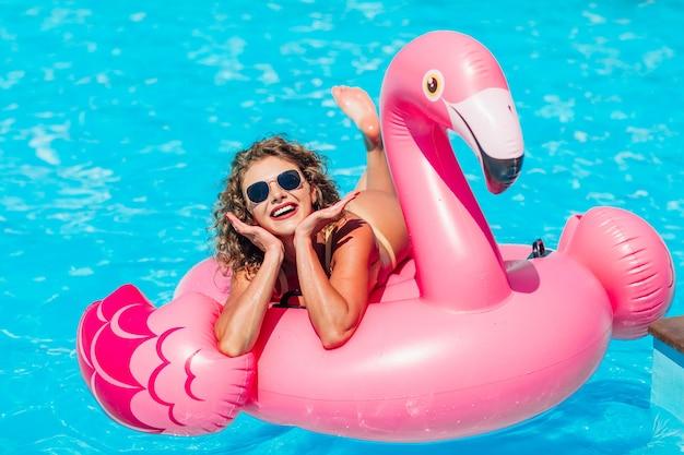 Chica rubia posando para historias de instsgram, descansando en la piscina de verano sobre un flamenco rosado inflable en traje de baño.