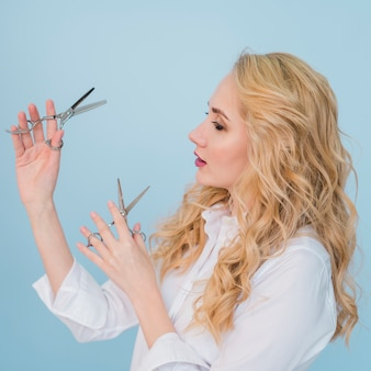 Chica rubia posando con tijeras