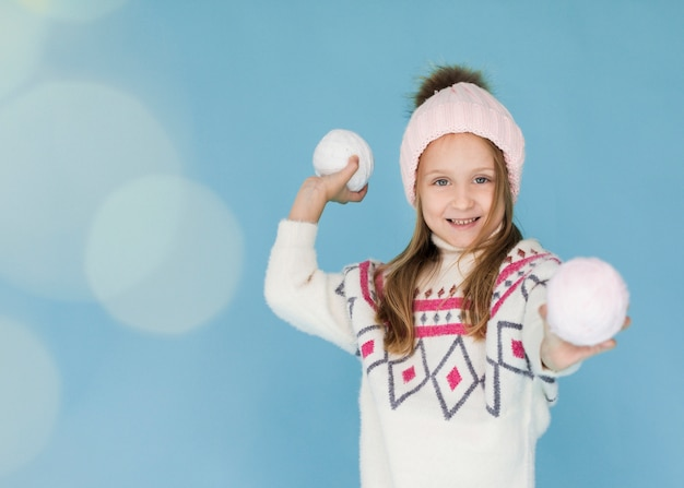Chica rubia preparándose para lanzar una bola de nieve