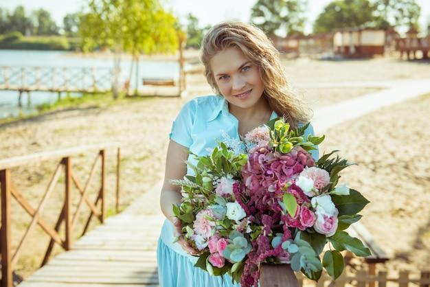 Chica rubia con ramo de flores en un vestido azul