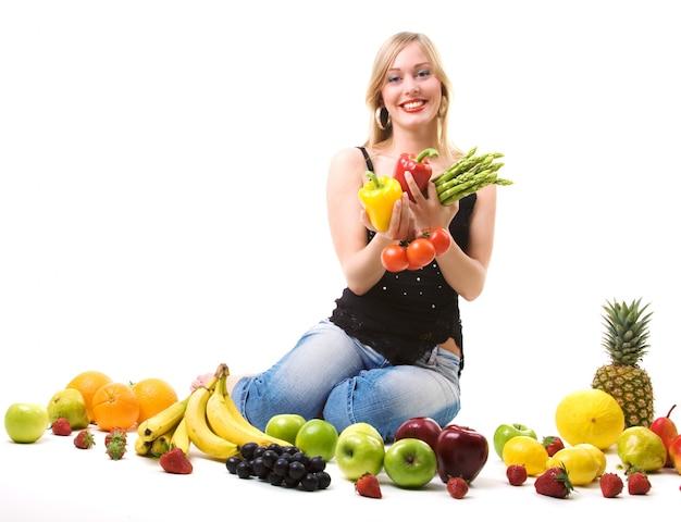 Chica rubia rodeada de frutas y verduras