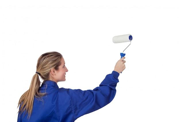 Chica rubia con un rodillo pintando una pared blanca