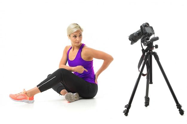 Chica rubia en ropa deportiva haciendo deporte delante de la cámara en blanco