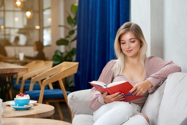 Chica rubia satisfecha leyendo un libro interesante sentado en la cafetería.