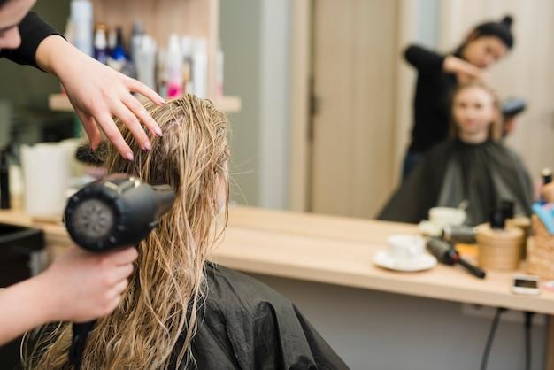 Chica rubia secándose el pelo