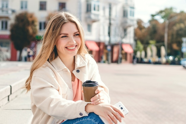 Chica rubia sentada en los escalones con una taza de café mira hacia otro lado y sonríe, copia espacio