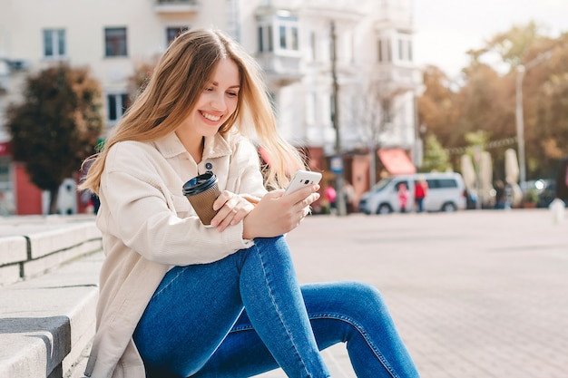 Chica rubia sentada en los escalones con un teléfono móvil riendo y enviando mensajes de texto con el mensajero