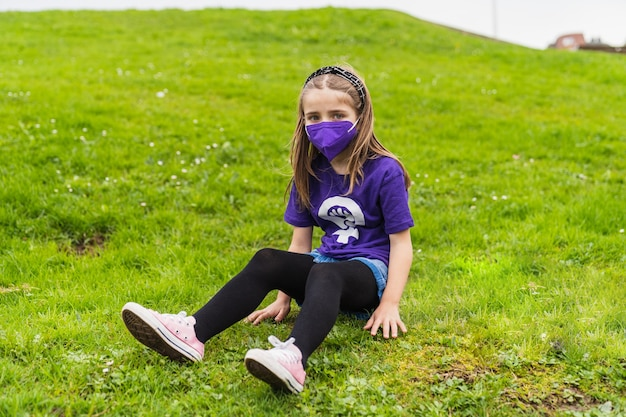 Chica rubia sentada libre en el césped de un parque con una camiseta morada con el símbolo feminista de las mujeres trabajadoras en el día internacional de la mujer, 8 de marzo y con una máscara por el coronavirus.