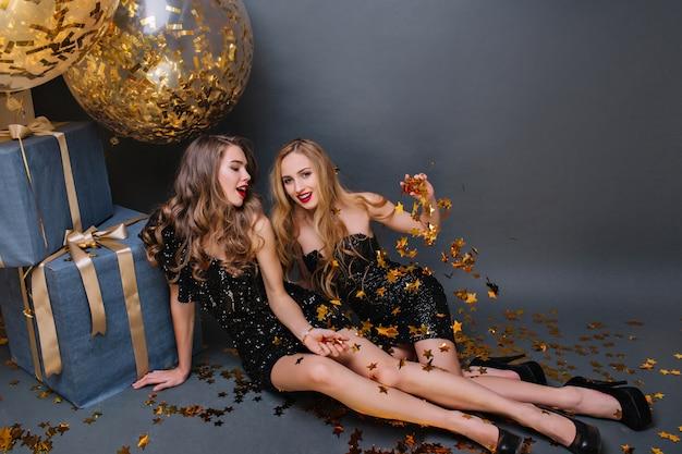 Chica rubia sentada en el suelo con un amigo y tirando confeti dorado. damas elegantes en vestidos negros junto a regalos y globos y bromeando.