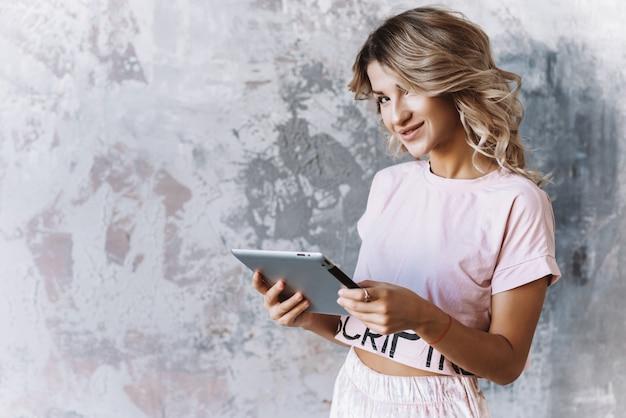 Chica rubia sosteniendo un ipad en sus manos