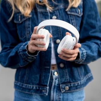 Chica rubia sosteniendo sus auriculares blancos