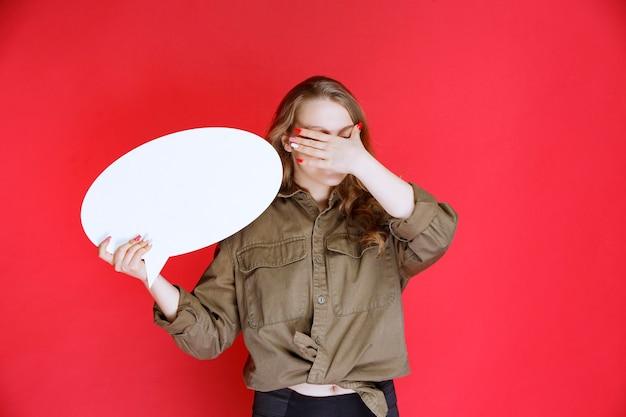 Chica rubia sosteniendo un tablero de proyectos ovales y no lo disfruta.