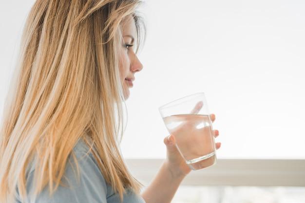Chica rubia sosteniendo vaso de agua