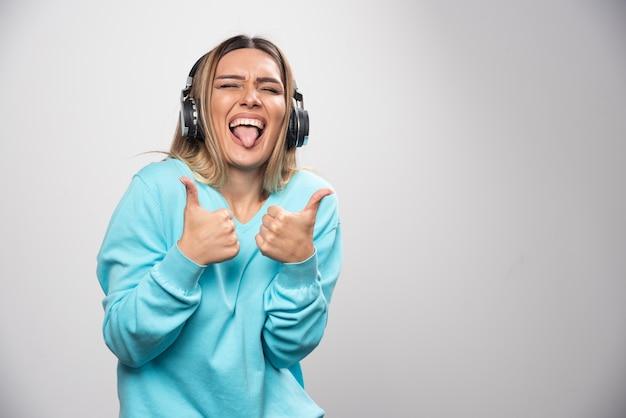 Chica rubia en sudadera azul con auriculares, disfrutando de la música y divirtiéndose