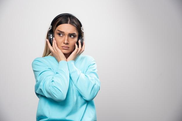 Chica rubia en sudadera azul con auriculares y tratando de entender la música.