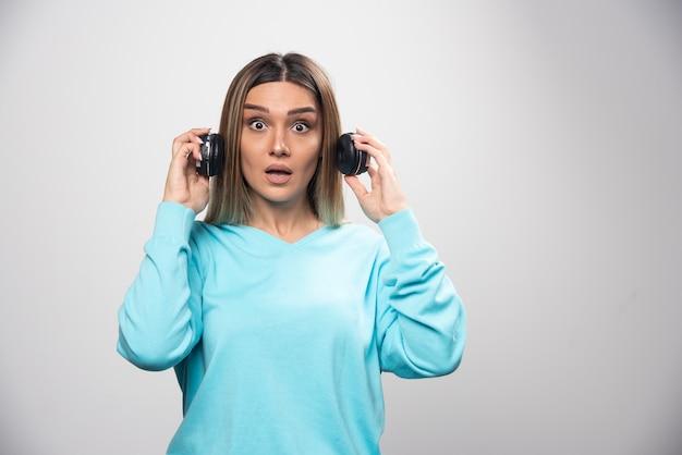 Chica rubia en sudadera azul sacando los auriculares para escuchar a la gente alrededor
