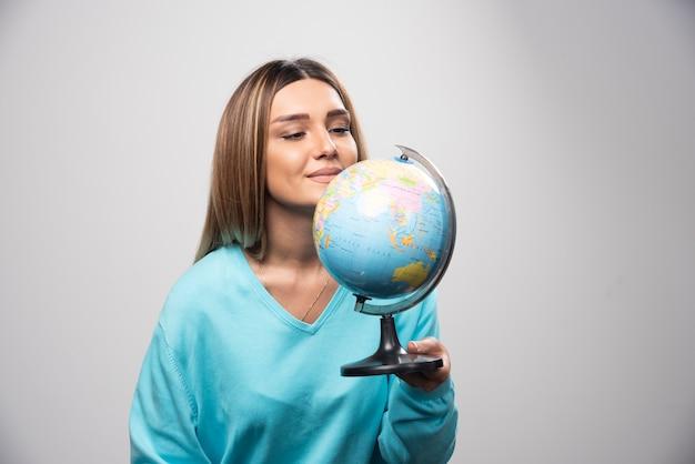 Chica rubia en sudadera azul sosteniendo un globo terráqueo, adivinando la ubicación y divirtiéndose.