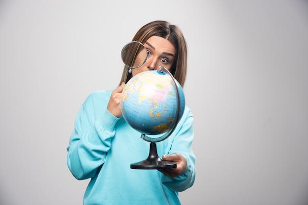 Chica rubia en sudadera azul sosteniendo un globo terráqueo y buscando un destino con lupa.