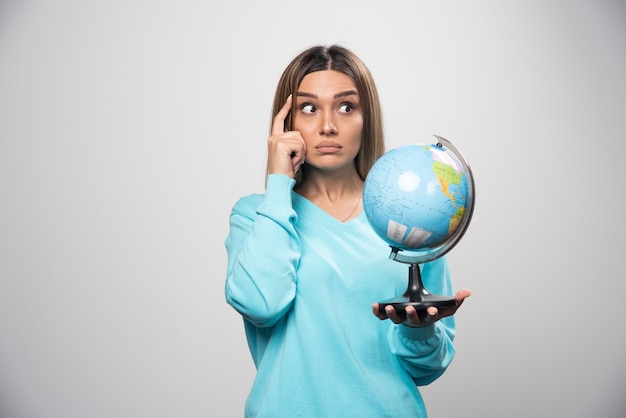 Chica rubia en sudadera azul sosteniendo un globo terráqueo, pensando cuidadosamente y tratando de recordar.