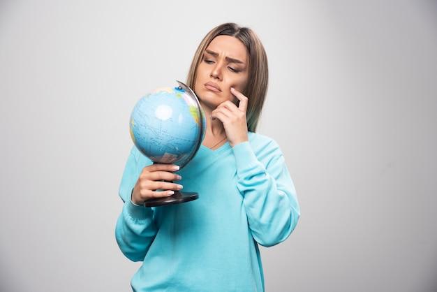 Chica rubia en sudadera azul sosteniendo un globo terráqueo, pensando cuidadosamente y tratando de recordar