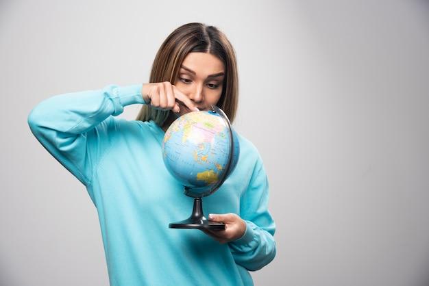 Chica rubia en sudadera azul sosteniendo un globo terráqueo y revisando el mapa de la tierra con atención.
