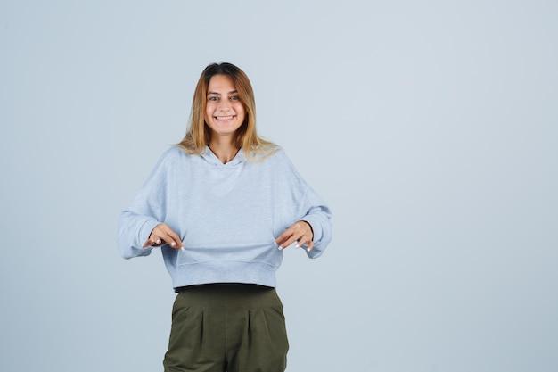 Chica rubia en sudadera azul verde oliva y pantalones tomados de la mano a la sudadera y mirando feliz, vista frontal.