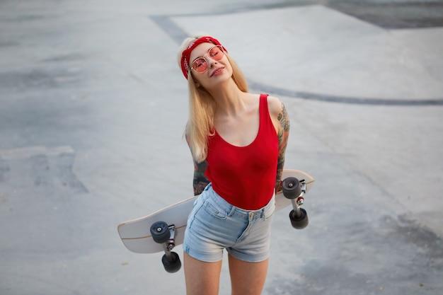 Chica rubia con tatuaje en gafas rojas, con camiseta roja y pantalones cortos de mezclilla, con pañuelo en la cabeza, sosteniendo un longboard en las manos, sonriendo de ensueño con los ojos cerrados, disfruta del tiempo en el skate park.