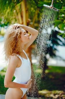 Chica rubia tomando una ducha junto a la piscina