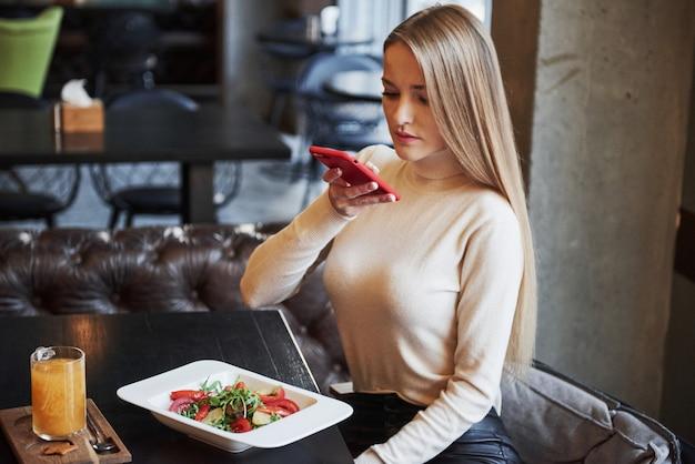 Chica rubia tomando foto de ensalada de verduras en el restaurante