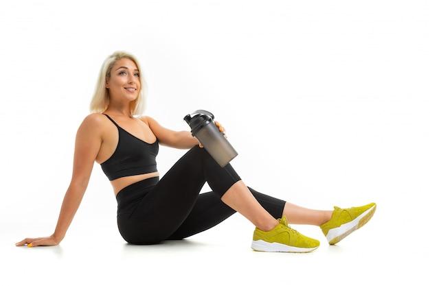 Chica rubia en uniforme deportivo se sienta en el suelo con una botella de agua en blanco