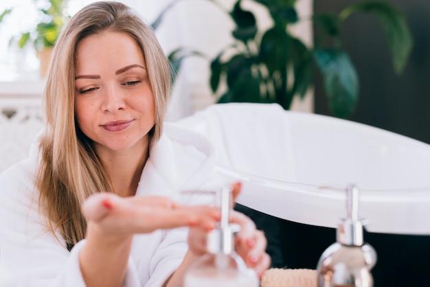 Chica rubia usando jabón en el baño