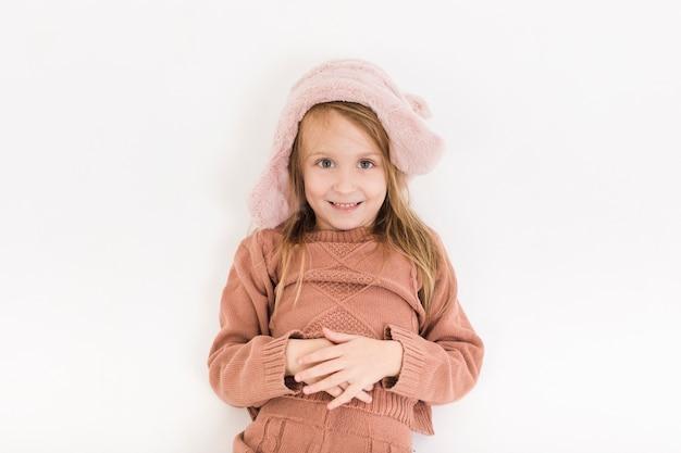 Chica rubia vestida de invierno mirando al fotógrafo