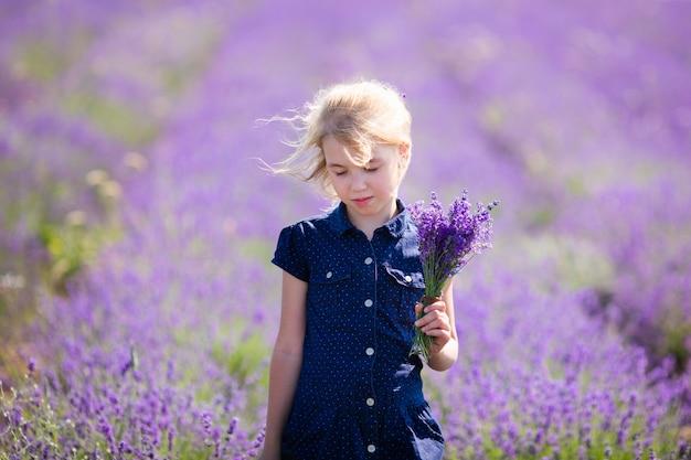 Chica rubia en el vestido azul en el campo de lavanda con un pequeño bouqet de flores