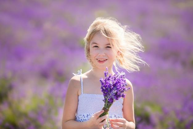 Chica rubia en el vestido azul en el campo de lavanda que huele un pequeño bouqet de flores